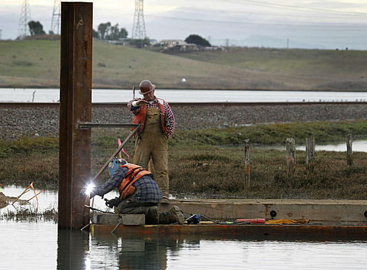 A construction crew works at Elkhorn Slough in Moss Landing, Calif., on Wednesday, Dec. 8, 2010. Conservationists are constructing a sill, a submerged steel wall designed to slow the outgoing tidal flow, in an effort to reduce erosion and protect the habitat of hundreds of marine species.