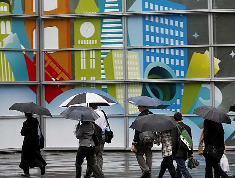 On Fourth Street near downtown San Francisco, people hurried past a mural for a salesforce.com convention in town. Umbrellas were a common sight in most of the Bay Area Wednesday, December 8, 2010 , as a stubborn rain fell most of the day. Photo: Brant Ward, The Chronicle