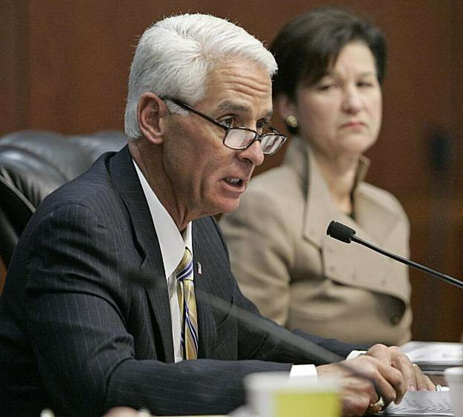 Florida Gov. Charlie Crist reads a statement listing his reasons for pardoning the late rock star Jim Morrison as cabinet member Alex Sink listens on Thursday, Dec. 9, 2010 in Tallahassee, Fla. Photo: Steve Cannon, AP