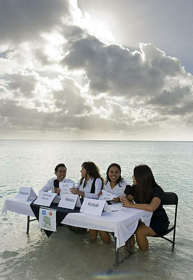 Ana Oposa (R) and Christopher Yu (L), members of delegations from the Philippines, share a table in the sea with Australian Ody Kamal (2-R) and Dominican Vanesa Taveras (2-L), both members of the NGO 350.org, representing a negotiation table regarding theislands in danger of disappearing due to the rising ocean levels caused by global warming, in the framework of the COP16 United Nations Climate Change conference on December 9, 2010 in Cancun, Mexico. Photo: Omar Torres, AFP/Getty Images