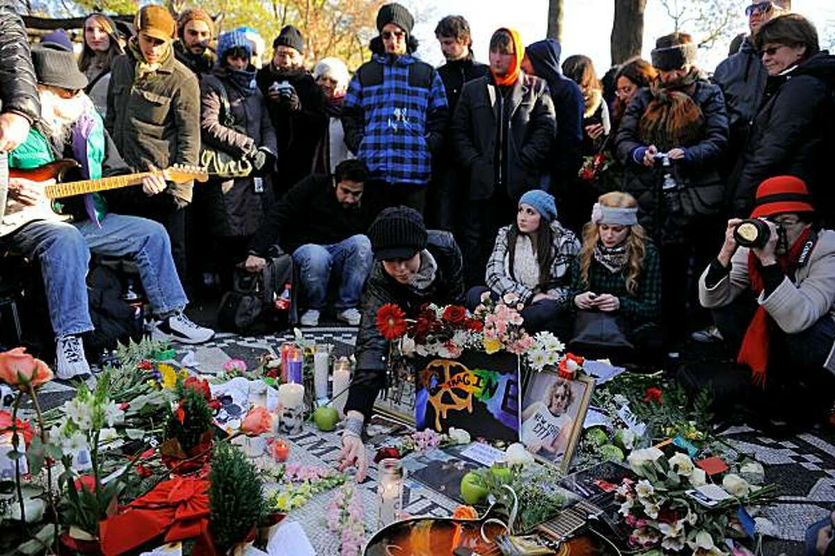 NEW YORK, NY - DECEMBER 08: Fans and well wishers gather at the Strawberry Fields Memorial to sing songs and leave flowers as they commemorate the 30th anniversary of the death of John Lennon in Central Park on December 8, 2010 in New York City.