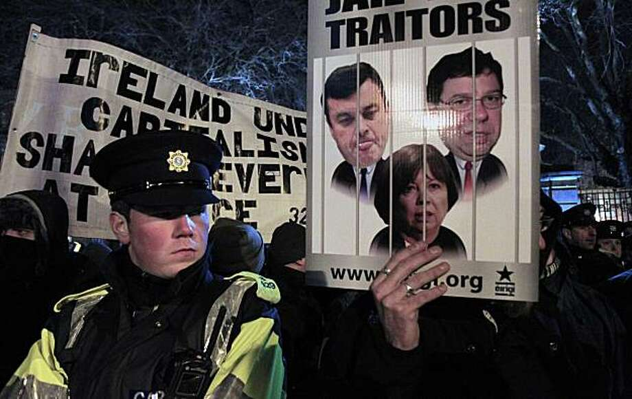 A policeman stands guard as protestors hold a demonstration outside Leinster House, Dublin, Ireland, Tuesday, Dec. 7, 2010. Lawmakers narrowly approved tax hikes Tuesday as part of Ireland's most brutal budget in history, a euro6 billion ($8 billion) slash-and-tax plan imposed as a key condition of the nation's international bailout. Rejection following Tuesday's publication of the long-awaited 2011 budget would have forced Prime Minister Brian Cowen's resignation and snap elections and raised doubts about whether Ireland could tap Û67.5 billion ($90 billion) from the European Union and the International Monetary Fund. Photo: Peter Morrison, AP