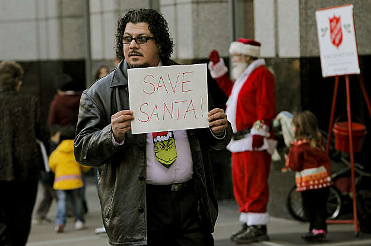 Xavier Montaigu and his 4-year-old daughter Isabel, (with Salvation Army Santa), of Benicia show their support for Santa John, on Tuesday Dec. 7, 2010, who had been a fixture around the Christmas holidays as the Santa at Macy's before he was fired yesterday for candid remarks that some patrons found offensive. They protest the firing in front of Macy's Union Square San Francisco, Calif.