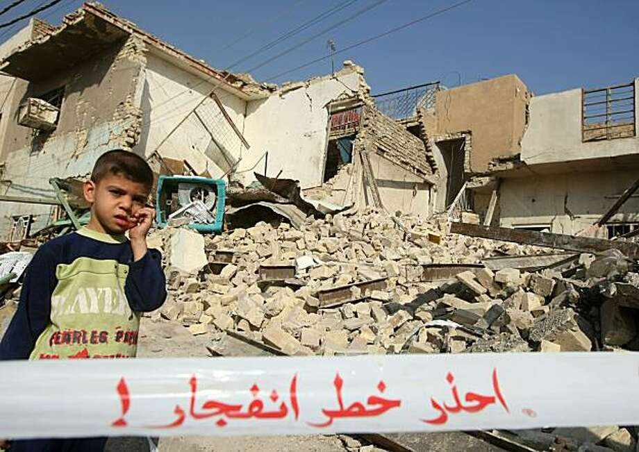 "An Iraqi boy stands behind a cordoned-off area near a destroyed rest house popular with Iranian religious tourists, which was targeted by a blast the day before killing five Iranian pilgrims and wounding 18 others, in the Kadhimiya district of Baghdad onDecember 5, 2010. Warning on strap reads ""Warning: Danger of explosion"". Photo: Ahmad Al-rubaye, AFP/Getty Images"