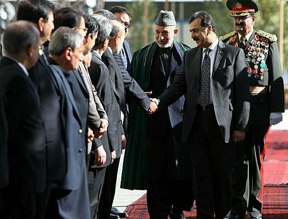 "Afghanistan's President Hamid Karzai (C) and Pakistani Prime Minister Yusuf Raza Gilani (2R) shake hands with Afghan officials during a welcoming ceremony in Kabul on December 4, 2010. Gilani, on the first day a two-day visit to Kabul, along with Karzai downplayed the leaked US cables, saying they were merely the ""views of junior officers."" Photo: S. Sabawoon, AFP/Getty Images"