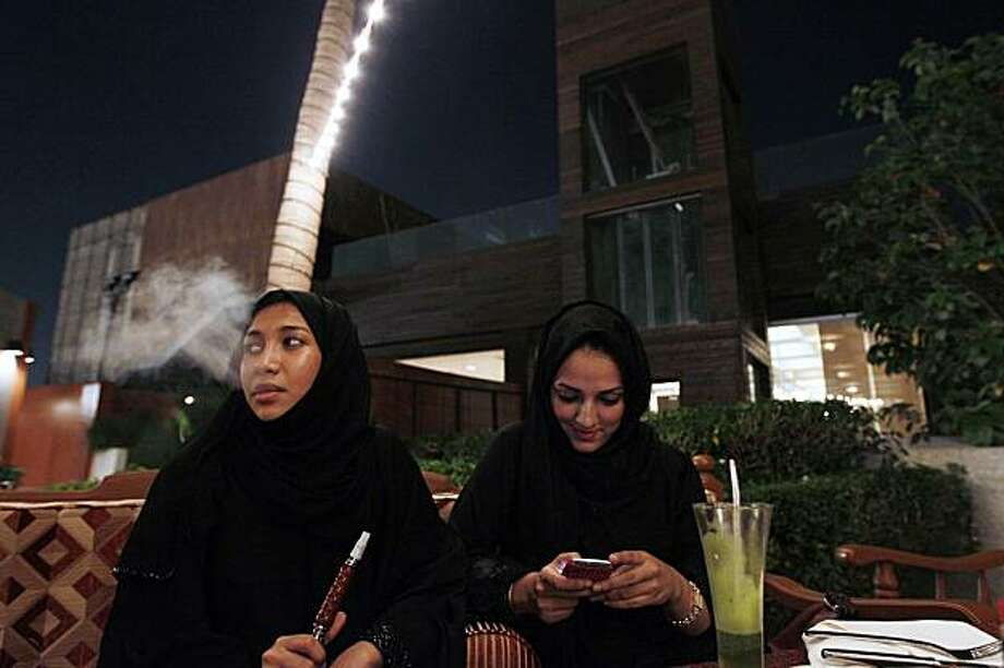 In this Nov. 11, 2010 photo, a Saudi woman smokes tobacco from a water pipe as her friend looks at her cell phone in a coffee in Jeddah , Saudi Arabia. Photo: Hassan Ammar, Associated Press