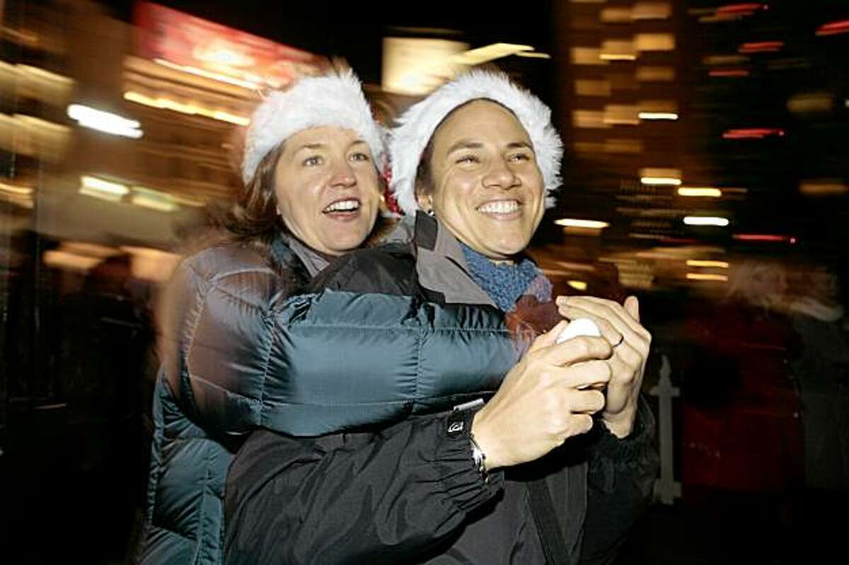 Click through this slideshow to see images of Union Square around the Holidays. Melody Moore, left, and Stacey Cobalt watch the lighting of an 85-foot Christmas Tree at Union Square on Friday in San Francisco.