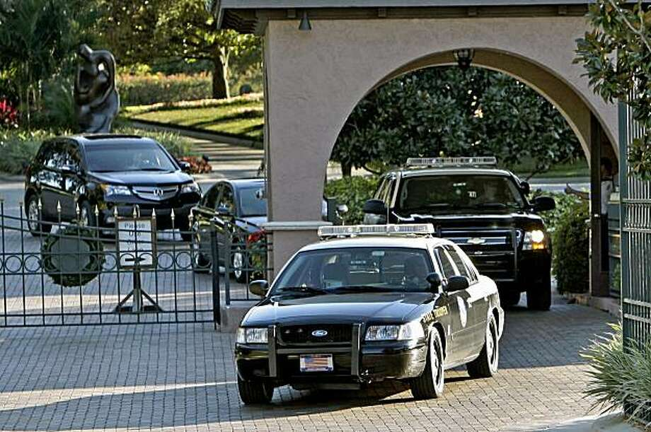Two vehicles with the Florida Highway Patrol exit the front gate of Isleworth where Tiger Woods lives in Windermere, Fla., Sunday, Nov. 29, 2009 (AP Photo/John Raoux) Photo: John Raoux, AP