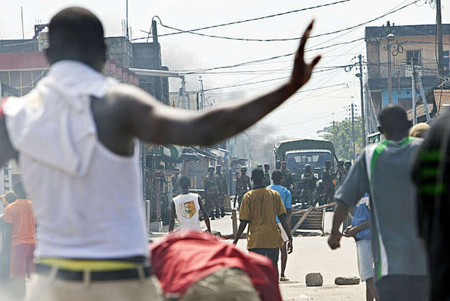 Supporter of opposition leader Alassane Ouattara face Ivorian troops in the street of Treichville neighborhood of Abidjan, Ivory Coast, Saturday, Dec. 4, 2010. The outcome of Ivory Coast's first presidential election in a decade was plunged into doubt Friday as the constitutional council declared incumbent President Laurent Gbagbo the winner a day after the election chief handed victory to the opposition. Photo: Thibault Camus, AP