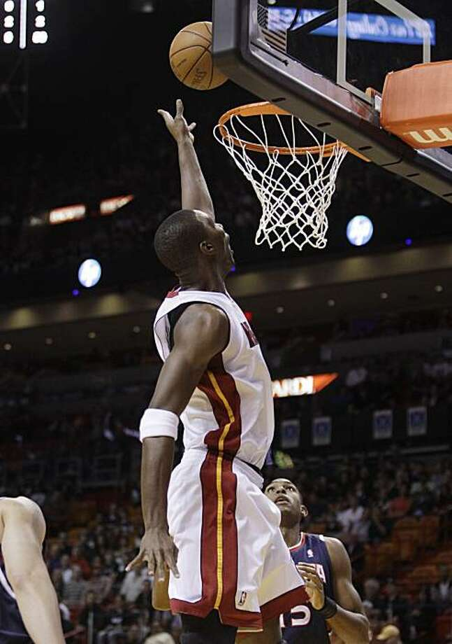 Miami Heat forward Chris Bosh shoots past Atlanta Hawks center Al Horford (15) in the first quarter during an NBA basketball game in Miami, Saturday, Dec. 4, 2010. Photo: Lynne Sladky, AP