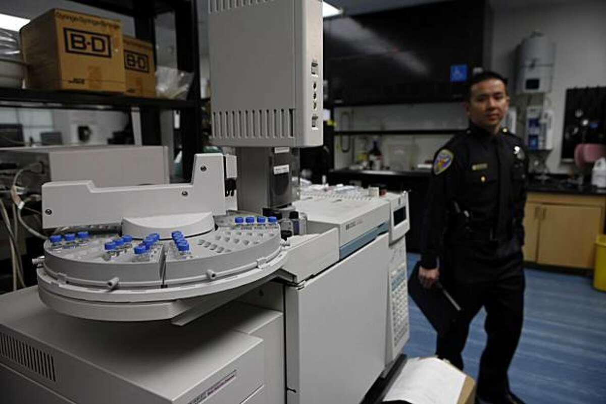 SFPD PIO Samson Chan (right) walks past equipment seen in the narcotics/chemical analysis unit during a media tour of the Crime Lab in San Francisco, Calif. on Wednesday, March 10, 2010.