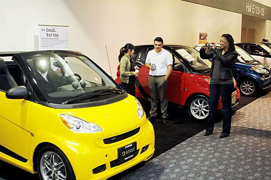 Car show visitors look over the new Smart Cars on display. The San Francisco International Auto Show starts at Moscone Center on Thursday, November 26, 2009, and attracts the top displays from the worldÕs major manufacturers. It is the largest show of any kind held in northern California. Photo: Carlos Avila Gonzalez, The Chronicle