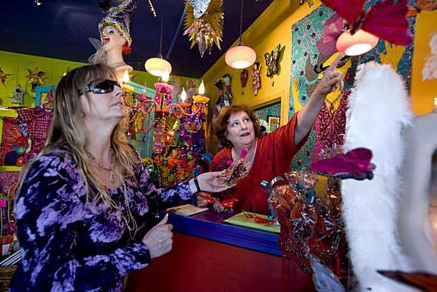 Kathryn Iniguez (left) of Hayward, Calif., shops in the store Tessuti Zoo as co-owner Emily Owens points to some items on the wall in Pacific Grove, Calif., on Wednesday, November 17, 2010. Photo: Chad Ziemendorf, Special To The Chronicle