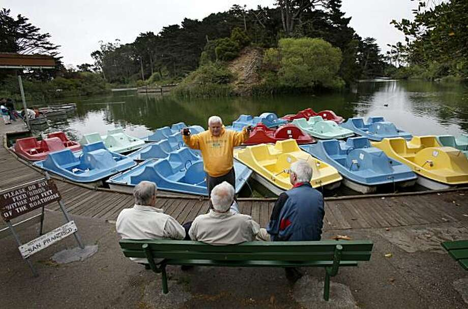 John Drocco (center) talks with some old friends near the boathouse.  He and others walk along the perimeter of Stow Lake for exercise. The Recreation and Parks Department of San Francisco, Calif. has been looking for a new vendor to take over concessions at the Stow Lake boat house. Photo: Brant Ward, The Chronicle
