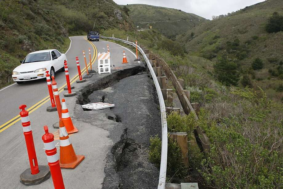 A car makes its way past a section of washed out road on Highway 1 near mile marker 4.80 in Marin Calif, on Friday March 25, 2011. Photo: Alex Washburn, The Chronicle