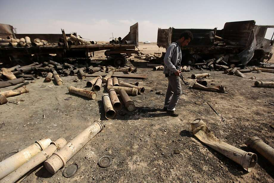 A Libyan rebel walks on March 27, 2011, past the remains of a pro-government ammunition convoy bombed the day before near Ajdabiya by coalition forces. Photo: Patrick Baz, AFP/Getty Images