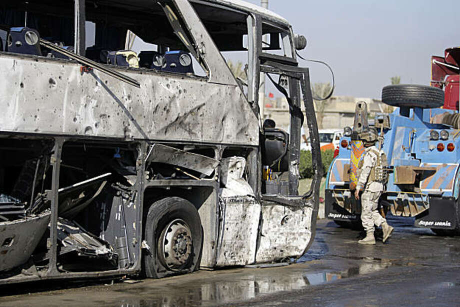 An Iraqi army soldier inspects a destroyed bus in Baghdad, Iraq, Saturday, Dec. 4, 2010. A car exploded next to a bus carrying Iranian pilgrims in the Shiite area of Shula, killing and wounding scores of people, police said. Photo: Hadi Mizban, AP