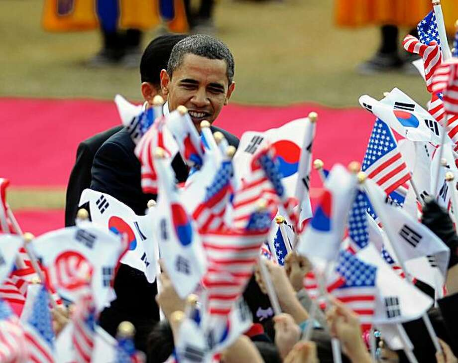 US President Barack Obama and South Korean President Lee Myung-bak (back) are greeted by children waving their respective national falgs during a welcome ceremony at the presidential Blue House in Seoul on November 19, 2009. Obama ends his maiden tour of Asia in Seoul with North Korea's nuclear programme and trade expected to be the main focus of a summit with Lee. AFP PHOTO/Mandel NGAN (Photo credit should read MANDEL NGAN/AFP/Getty Images) Photo: Mandel Ngan, AFP/Getty Images