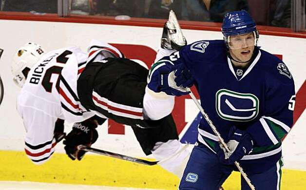 Vancouver Canucks' Christian Ehrhoff, right, of Germany, avoids a check from Chicago Blackhawks' Bryan Bickell during the first period of NHL hockey game action in Vancouve on Saturday, Nov. 20, 2010. Photo: Darryl Dyck, AP