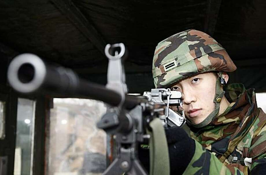 A South Korean Army solider aims his machine gun into a bunker at the Demilitarized Zone that separates the two Koreas in Cheorwon, South Korea, Thursday, Dec. 2, 2010. South Korean lawmakers slammed the government Thursday over revelations the country's spies failed to take seriously intelligence from August that indicated North Korea might attack a front-line island. (AP Photo/Yonahp, Lee Hae-ryoung)  KOREA OUT Photo: Lee Hae-ryoung, AP