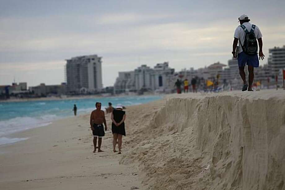 In this photo taken Nov. 9, 2010, people walk on a eroded beach in Cancun, Mexico. Cancun suffers from severe beach erosion problems caused by recent hurricanes and storms, and many unauthorized private efforts to mitigate the problem have helped to worsen the situation. Photo: Dario Lopez-Mills, AP