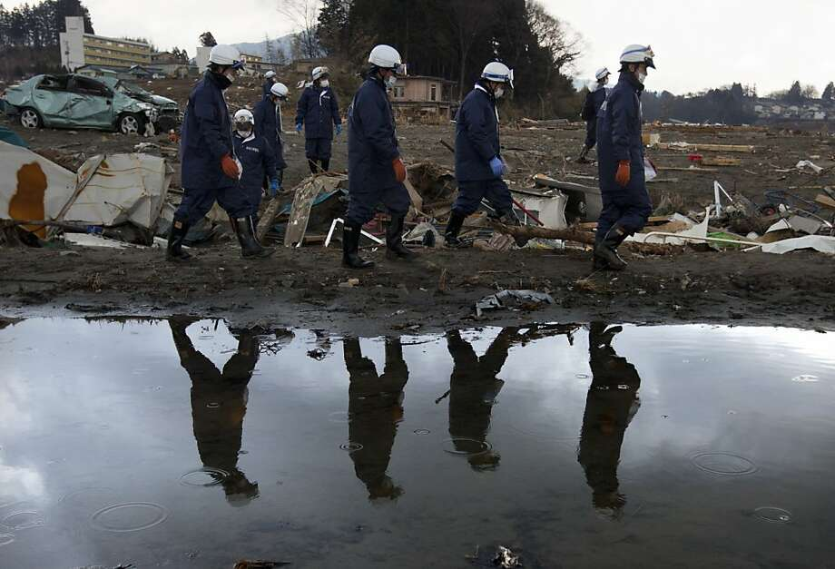 Japanese rescue teams comb  the rubble looking for more bodies March 27, 2011 in Kensennuma, Japan. More than two weeks after the magnitude 9 earthquake and tsunami struck Japan the death toll has risen to over 10,418 dead with still thousands missing and the expectation is that it will end up well over 20,000. Presently the country is still struggling to repair a damaged nuclear power plant that has caused tremendous problems, evacuations, and now tainted water supply in the Tokyo area causing more panic buying of bottled water. Photo: Paula Bronstein, Getty Images