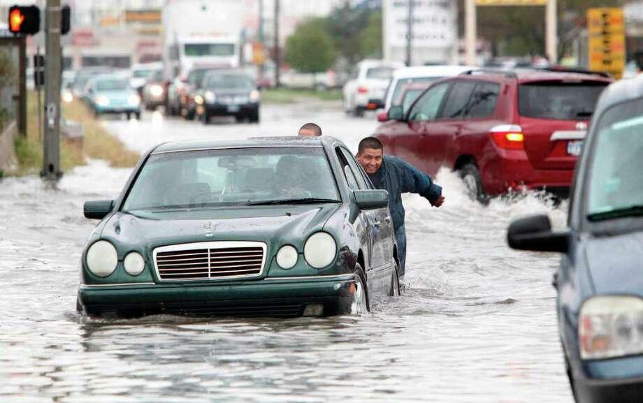 Luis Rodríguez ayuda, junta a otras personas, a un conductor de un vehículo que fue sorprendido por el nivel del agua acumulada en la intersección de Fondren y Harwin Drive tras el paso de la tormenta el lunes 9 de enero de 2012 en Houston. Photo: Mayra Beltran / © 2011 Houston Chronicle