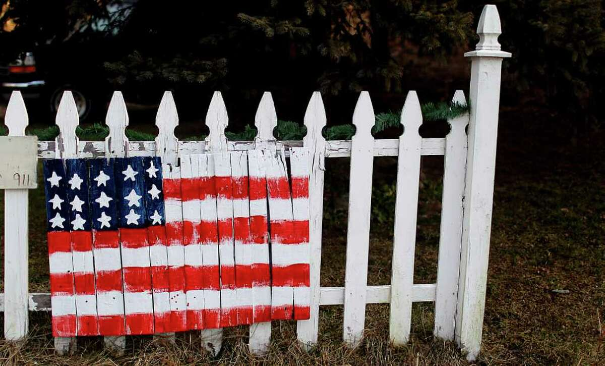 FILE. A picket fence decorated with an American flag in Londonderry, N.H., Jan. 10, 2012. (Cheryl Senter/The New York Times)