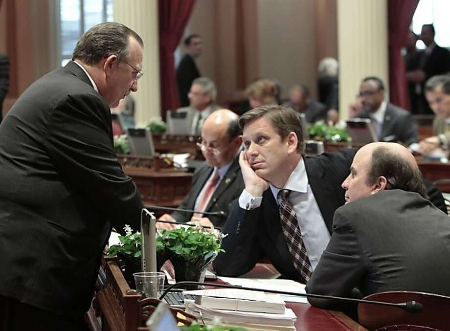 State Senate Minority Leader Bob Dutton, R-Rancho Cucamonga, left, talks with GOP lawmakers, Sen. Tony Strickland, R-Thousand Oaks, center, and Mark Wyland, R-Solana Beach during the debate over  Gov. Jerry Brown's state budget plan  at the Capitol in Sacramento,  Calif., Thursday March 17, 2011.  By a party-line vote, both houses of the legislature approved Brown's main budget bill but did not approve putting tax extensions before voters or eliminating redevelopment agencies. Photo: Associated Press, AP