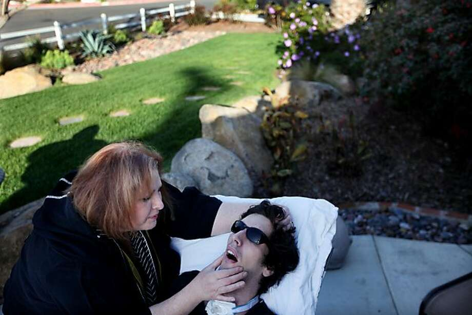 Madelyn Bennett shares a moment with her son John Gibson in their front yard at their home in San Diego on Friday March 11, 2011. Gibson suffered a heart attack while at UC Berkeley after ingesting illicit drugs and is now comatose.(Photo by Sandy Huffaker) Photo: Sandy Huffaker, Special To The Chronicle