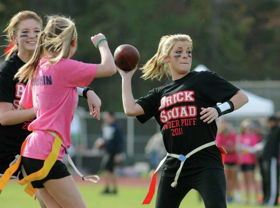 JERRY BAKER: FOR THE CHRONICLE GOING DEEP: Brick Squad quarterback Tyler Constantine, from right, looks for a receiver behind a block from teammate Mackenzie Haddock on Blitz Babes defender Sydney Duplechin during the 2nd Annual Team Joseph and Holley's Hope Powder Puff Football Tournament at Kingwood Park High School. Photo: Jerry Baker
