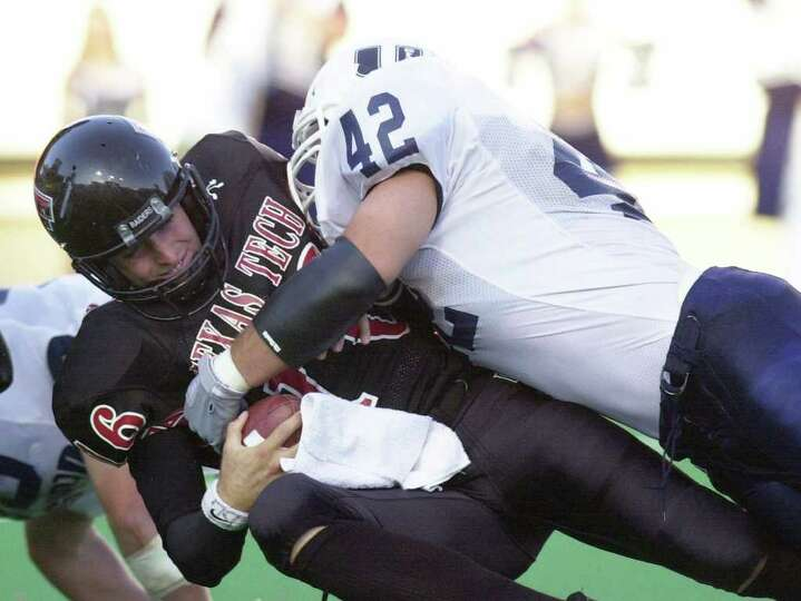 Texas Tech quarterback Kliff Kingsbury (16) is tackled by Utah State's Cade Smith (42) in the second