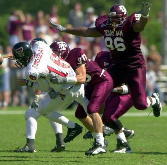 SPORTS/DAILY -- Texas Tech quarterback Kliff Kingsbury is sacked by Aggie players Keelan Jackson (#3
