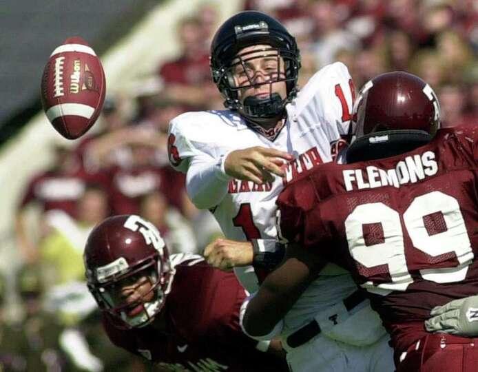 Texas Tech quaterback Kliff Kingsbury (16) is hit by Texas A&M's Ronald Flemons (99) as he throw