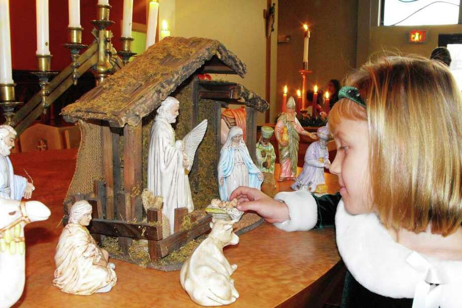 Karen Reilly Third grader, Meaghan Kienzle adds the final touch to All Saints Catholic Academy's Christmas manger at a recent prayer service,
