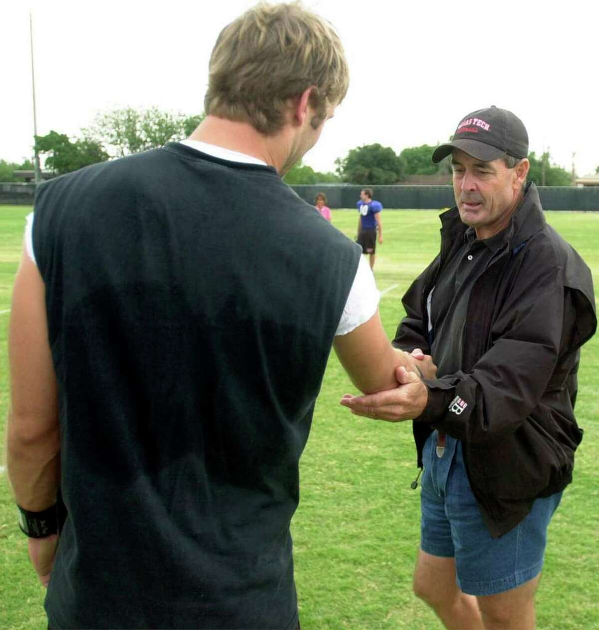 Tim Kingsbury, father of Kliff Kingsbury, mentored his son throughout high school and college football, being a former football coach himself. In this photo, Tim, right, checks out the arm of Kliff after practice Saturday morning, Aug. 10, 2002, at the Texas Tech football practice field in Lubbock, Texas.