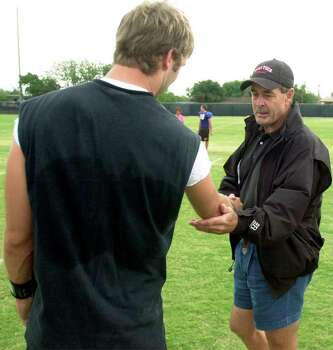 Tim Kingsbury, right, a former high school football coach, checks out the arm of his son, Kliff, after practice Saturday morning, Aug. 10, 2002, at the Texas Tech football practice field in Lubbock, Texas. Kliff Kingsbury, quarterback for the Texas Tech Red Raiders, led the league in passing during his junior year, with 3,502 yards and 25 touchdowns. Photo: ROBIN M. CORNETT, AP / LUBBOCK AVALANCHE-JOURNAL