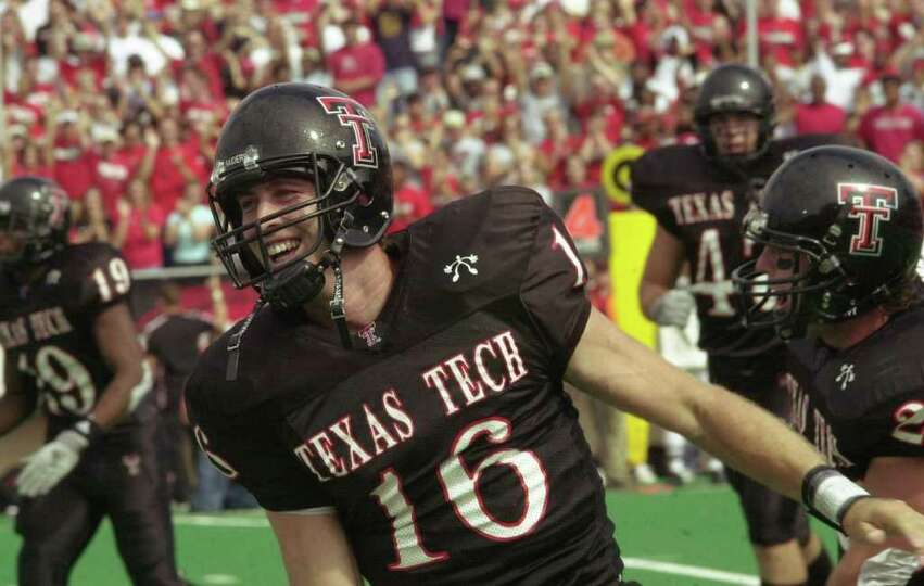Texas Tech quarterback Kliff Kingsbury (16) celebrates while heading to the sidelines during the fir