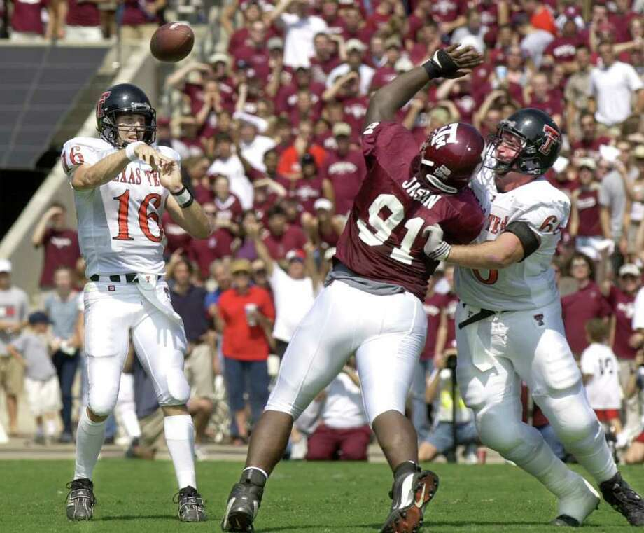 Texas Tech's Kliff Kingsbury (16) throws a pass over Texas A&M's Marcus Jasmin (91) being blocked by Toby Cecil (66) in the first quarter Saturday, Oct. 5, 2002, in College Station, Texas.  Kingsbury threw for 474 yards and five touchdowns in a 48-47 Texas Tech overtime win. Photo: BRETT COOMER, AP / AP