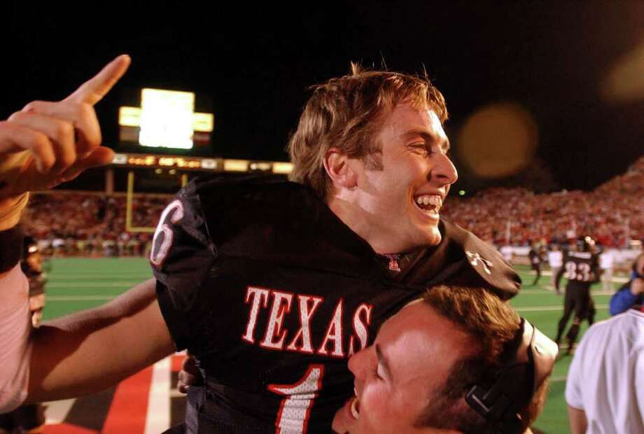 SPORTS - Tech quarterback Kliff Kingsbury celebrates with headf coach Mike Leach (???) after knocking off the Longhorns 42-38. !!NOTE!!- WILL DOUBLE CHECK IF THE COACH IS LEACH AND GET BACK TO YOU.  BAHRAM MARK SOBHANI/STAFF TEXAS AT TEXAS TECH SATURDAY, NOVEMBER 16, 2002 JONES SBC STADIUM Photo: BAHRAM MARK SOBHANI, SAN ANTONIO EXPRESS-NEWS / SAN ANTONIO EXPRESS NEWS
