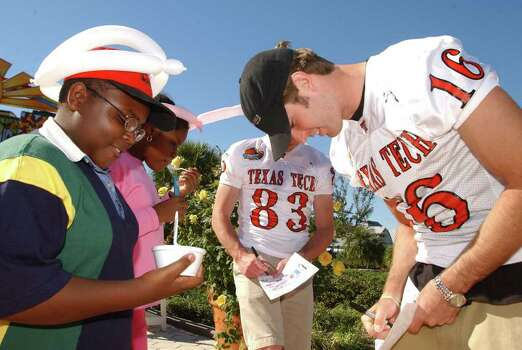 Texas Tech players Kliff Kingsbury, right, and Slade Hodges sign autographs for Westley Brown, 12, left, of Kissimmee, Fla., and his sister, Kristine, 11, during a visit to the Give Kids the World Village in Kissimmee, Sunday, Dec. 22, 2002. Players from Clemson and Texas Tech visited the children as part of the Tangerine Bowl activites. Photo: PHELAN M. EBENHACK, AP / AP