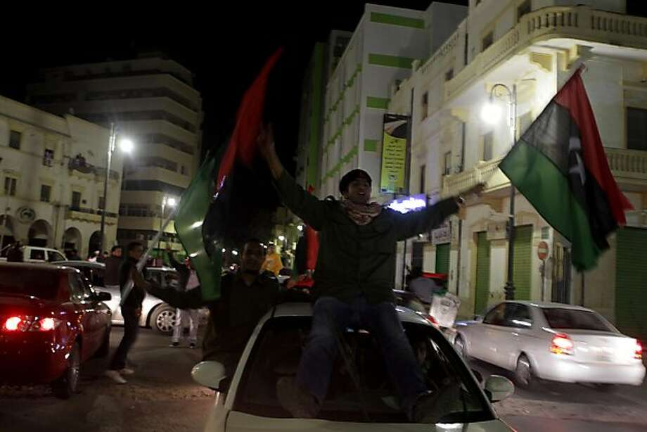 "Libyans wave the flag of the Kingdom of Libya used by the rebellion in the center of Benghazi on March 17, 2011 as people gathered in the street in defiance after Libyan leader Moamer Kadhafi announced an imminent assault on the city. Moamer Kadhafi saidhe would launch an assault on rebel stronghold Benghazi night and show the ""traitors"" no mercy,"" as world powers edged towards tough measures that could see air strikes against his forces begin in hours. Photo: Patrick Baz, AFP/Getty Images"