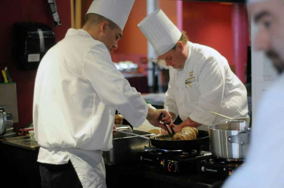 "Chefs, from left, Paul Hill, Paul Karlson and Eric DesRosiers of Skidmore College prepare their dishes during a cooking competition at the Skidmore College dining hall on Tuesday, Jan. 10, 2012 in Saratoga Springs, NY.  The college was hosting 10 culinary teams from regional colleges for a two-day conference titled ""Healthy Foods, Sustainable Choices.""   (Paul Buckowski / Times Union) Photo: Paul Buckowski"