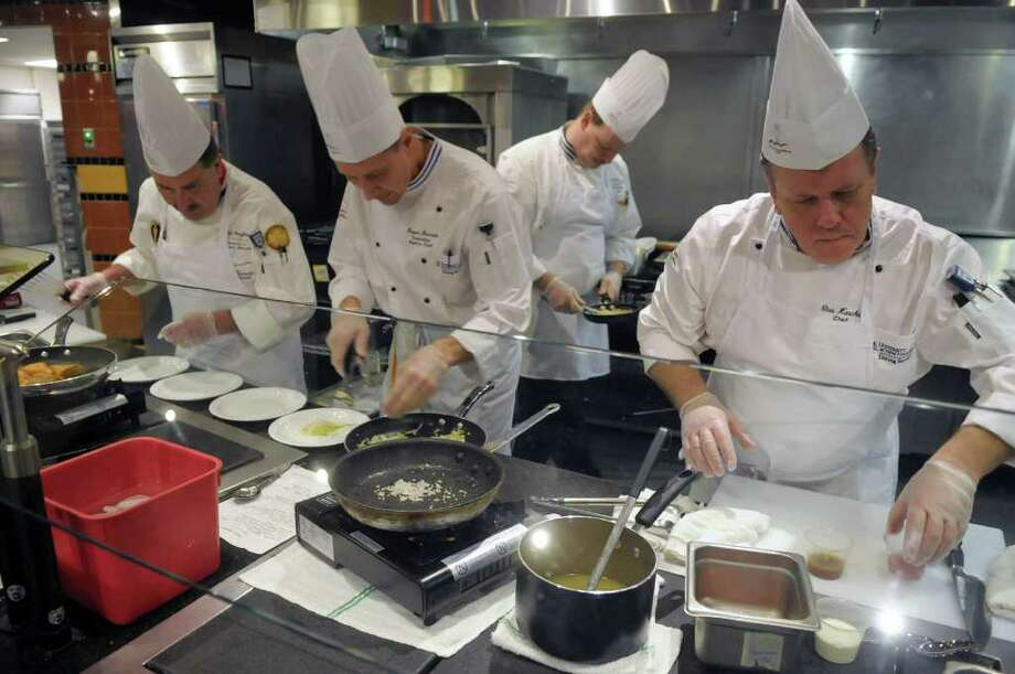 "Chefs from the University of New Hampshire work on their dishes during a cooking competition at the Skidmore College dining hall on Tuesday, Jan. 10, 2012 in Saratoga Springs, NY.  The college was hosting 10 culinary teams from regional colleges for a two-day conference titled ""Healthy Foods, Sustainable Choices.""   (Paul Buckowski / Times Union) Photo: Paul Buckowski"