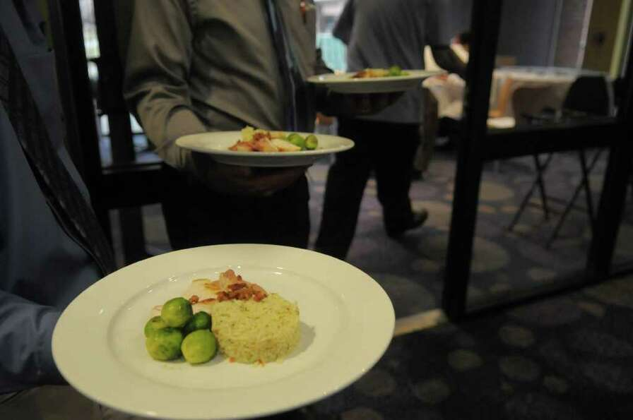 Dishes from a team are taken in for judges to taste during a cooking competition at the Skidmore Col