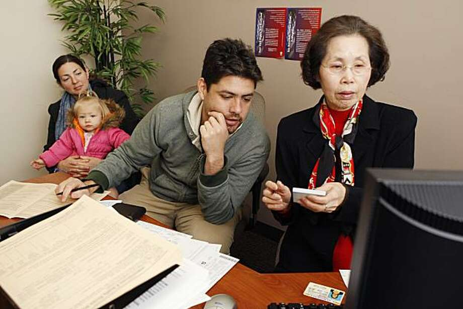 Stephanie, Sophia and David Moore (left to right) sit with Jen Kang as she prepares their taxes for free at The Cooperative Centeral Federal Credit Union in Berkeley Calif, on Thursday, Feb. 24, 2011. Kang has worked at the credit union for 15 years but this is her first time volunteering for the free tax preparation program. Photo: Alex Washburn, The Chronicle