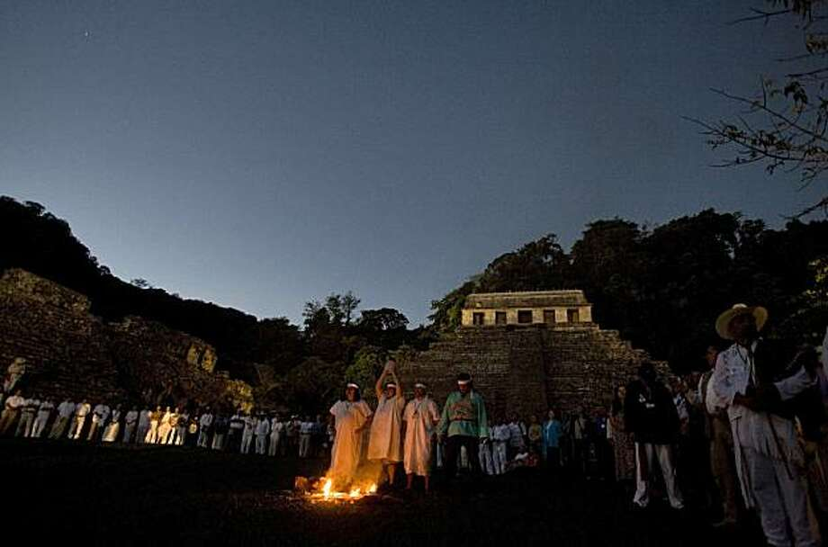 People watch as Mayan priests participate in a ceremony while one holds up a crystal skull at the  ruins of Palenque. There is a legend that the ancient Maya possessed 13 crystal skulls which, when united, hold the power of saving the Earth. Photo: Alexandre Meneghini, AP