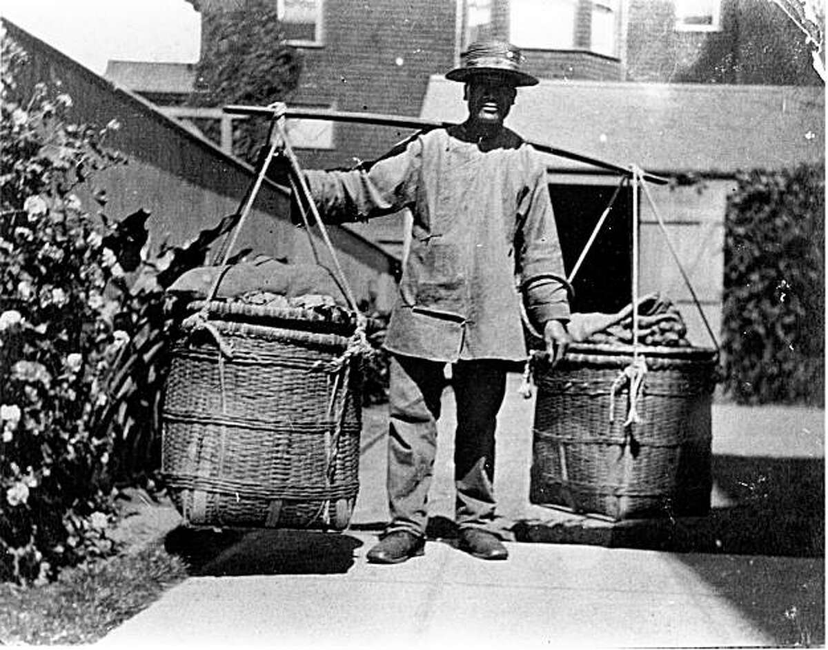 A Chinese man in traditional clothing carries a load in the East Bay. The weight of his load is evident in the pole bending across his shoulders. Photo from Richard Schwartz's book 'Berkeley 1900: Daily Life at the Turn of the Century.'