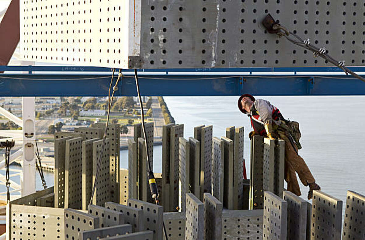 An ironworker works on the Bay Bridge Self-Anchored Suspension Span as a section of the tower for the new bridge is lowered into place at the construction site in San Francisco, Calif., on Monday, February 28, 2011.