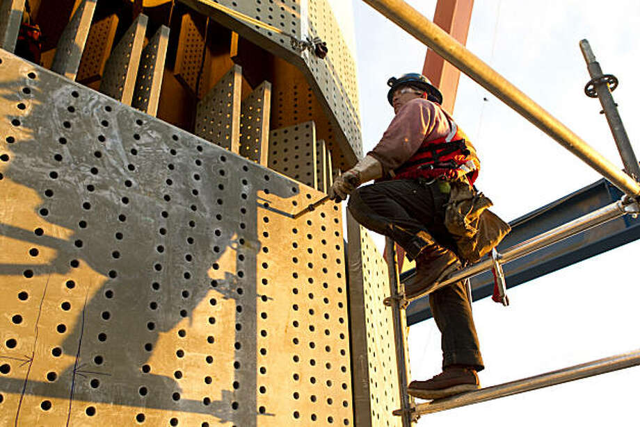 An ironworker works on the Bay Bridge Self-Anchored Suspension Span as a section of the tower for the new bridge is lowered into place at the construction site in San Francisco, Calif., on Monday, February 28, 2011. Photo: Laura Morton, Special To The Chronicle